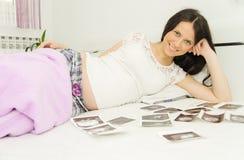 Gravida kvinnan tycker om att se ultraljudsundersökning av behandla som ett barn Royaltyfri Fotografi