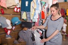 Gravida kvinnan väljer barnet för kläder inför framtiden i lager Royaltyfria Foton