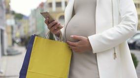 Gravida kvinnliga shoppa påsar som beställer taxien vid smartphoneapplikation, grej arkivfilmer