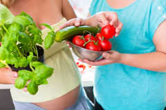 Gravida kvinnor med sunda grönsaker Arkivfoto