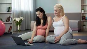 Gravida kvinnor som beskådar websites på bärbara datorn, online-shopping för framtida mammor royaltyfri foto