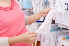 Gravida kvinnor som köper kläder för henne, behandla som ett barn Royaltyfria Foton