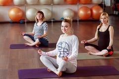 Gravida kvinnor som kopplar av genom att använda yoga, poserar Arkivbild