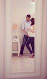 Gravida par för barn i spegeln Arkivfoto
