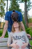 Gravida par för barn - skratta som är utomhus- Royaltyfria Bilder