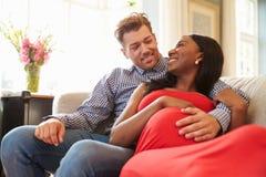 Gravida par hemma som kopplar av på Sofa Together arkivfoton
