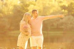 Gravida par i strålarna av solljus på solnedgången Makekramar Arkivfoto