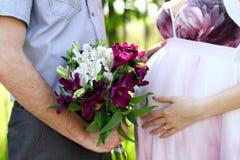 Gravida par med buketten av blommor i en sommar parkerar fotografering för bildbyråer