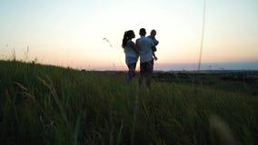 Gravida par med litet barndottern har fritid utomhus på solnedgången arkivfilmer