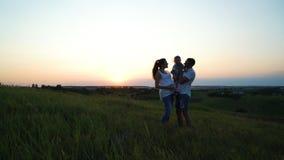 Gravida par med litet barndottern har fritid utomhus på solnedgången royaltyfria bilder
