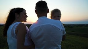 Gravida par med litet barndottern har fritid utomhus på solnedgången royaltyfri foto
