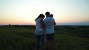 Gravida par med litet barndottern har fritid utomhus på solnedgången lager videofilmer