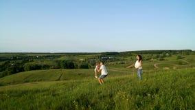 Gravida par med litet barndottern som går i gräsplanfält som har fritid lager videofilmer