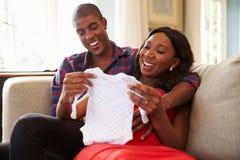 Gravida par på Sofa At Home Looking At behandla som ett barn kläder arkivfoton