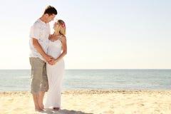 Gravida par som är förälskade på stranden fotografering för bildbyråer