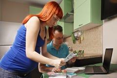 Gravida par som gör skrivbordsarbete Arkivfoton