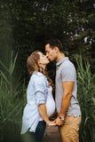 Gravida parinnehavhänder och kyssa sig royaltyfria bilder