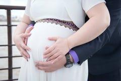 Gravida parinnehavhänder på magen Royaltyfria Bilder