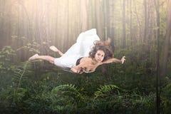 Gravidade zero Voo bonito novo da mulher em um sonho Verde floresta e fulgor imagem de stock