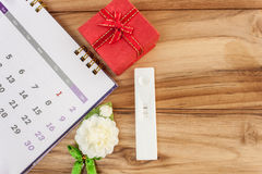 gravidanza e contenitori di regalo rossi del calendario su un di legno Fotografie Stock