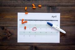Gravidez do planeamento Teste de gravidez positivo perto da página do calendário e comprimidos na opinião superior do fundo de ma Imagem de Stock