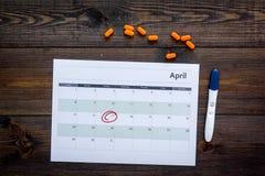 Gravidez do planeamento Teste de gravidez positivo perto da página do calendário e comprimidos na opinião superior do fundo de ma Imagens de Stock Royalty Free