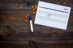 Gravidez do planeamento Teste de gravidez positivo perto da página do calendário e comprimidos no espaço de madeira escuro da cóp Fotos de Stock