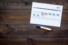 Gravidez do planeamento Teste de gravidez positivo perto da página do calendário e comprimidos no espaço de madeira escuro da cóp Imagens de Stock