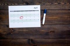 Gravidez do planeamento Teste de gravidez positivo perto da página do calendário no espaço de madeira escuro da cópia da opinião  Fotos de Stock