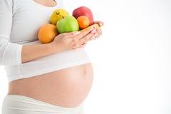A gravidez e a nutrição fazem dieta - a mulher gravida com isolat dos frutos imagem de stock