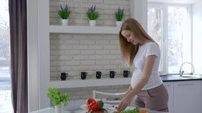Gravidez e nutrição saudável, menina bonita que corta vegetais e que come o tomate que guarda sua barriga grande na cozinha vídeos de arquivo