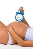 Gravidez feliz Barriga grávida com despertador Logo nascimento fotografia de stock royalty free