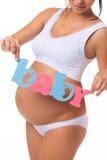 """Gravidez motherhood Texto azul e cor-de-rosa """"Baby"""" na barriga grávida imagem de stock royalty free"""