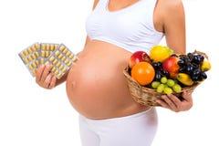 Gravidez saudável: comprimidos ou fruto? Close-up de uma barriga grávida Fotos de Stock