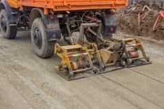 Gravier de compactage de camion au site de construction de routes Image stock