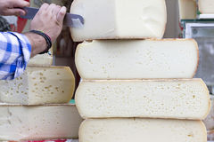 Graviera cheese. A stack of traditional, large Cretan graviera cheeses on display at a farmers' market Stock Photo