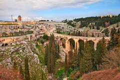 Gravina in Puglia, Bari, Italy: landscape of the the deep ravine. With the ancient aqueduct bridge, the old rock church Madonna della Stella and the cave houses Stock Photography