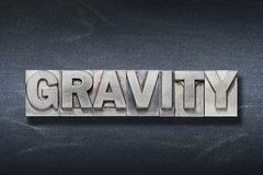 Gravity word den. Gravity word made from metallic letterpress on dark jeans background stock photo