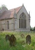 Gravstenar i en bevuxen kyrkogård Fotografering för Bildbyråer
