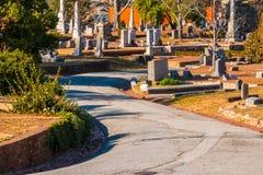 Gravstenar, träd och väg på den Oakland kyrkogården, Atlanta, USA Arkivbild