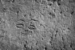 Gravure antique du visage sur un mur en pierre Photo libre de droits