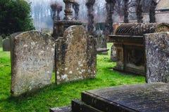 Gravvalv och gravstenar i ett typisk engelska kyrktar kyrkogården royaltyfria bilder