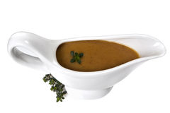 Gravy. Thyme gravy in white gravy boat, isolated.  Delicious Royalty Free Stock Photos