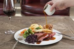 Gravy being poured on to roast dinner. A meal of rare roast beef with carrots, sprouts, parsnips and red cabbage with gravy pouring and a glass of red wine stock image