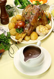 Gravy Boat With Lamb Leg. Gravy boat with roasted lamb leg and vegetables royalty free stock image