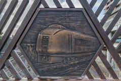 Gravyr på metall som föreställer det toppna Hitachi drevet på den Shimogoindenbashi bron som når Nipporien och Yanakaen arkivbild