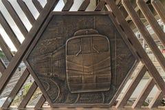 Gravyr på metall som föreställer ett drev på den Shimogoindenbashi bron som når de Nippori och Yanaka grannskaparna royaltyfri foto