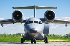 Gray Airplane com os motores nas asas estacionou no parque de estacionamento no aeroporto Fotografia de Stock