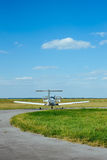 Gray airplane parked on the grass at the airfield Stock Photo