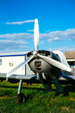 Gray airplane parked on the grass at the airfield Royalty Free Stock Images